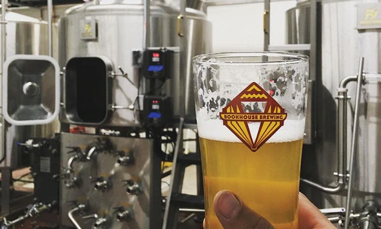 Bookhouse Brewing's brewhouse with tasting glass foreground.