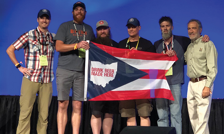 Brink Brewing representatives accept a medal at the Great American Beer Festival while holding a Drink Beer Made Here Ohio flag